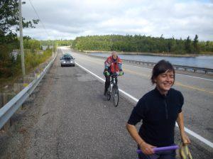 Coureuse Giroflée Arsenault suivie par Geneviève Huchette sur vélo, traversant le Parc de la Vérendrye